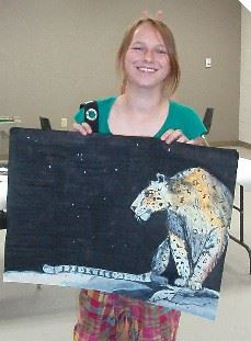 Smiling woman showing her art work of a large cat