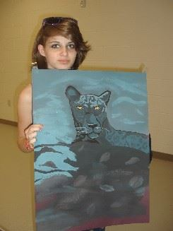 Woman with a painting of a dark colored cat with yellow eyes